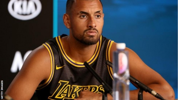 Nick Kyrgios wearing an LA Lakers shirt in a post-match news conference