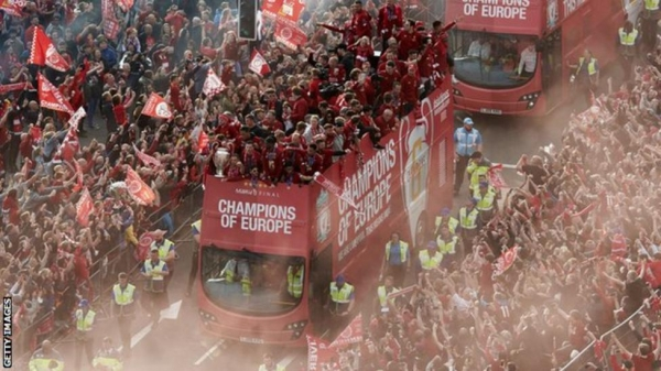 Thousands of fans line the streets as Liverpool parade the Champions League trophy on an open top bus